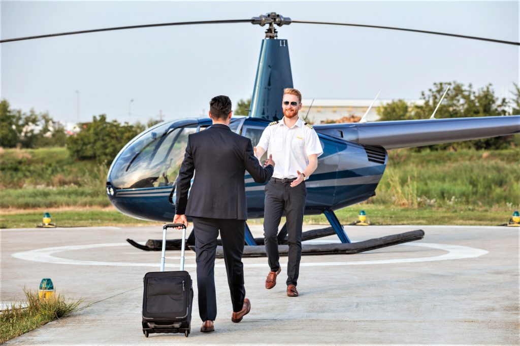 Helicopter pilot and passenger meeting by the helicopter